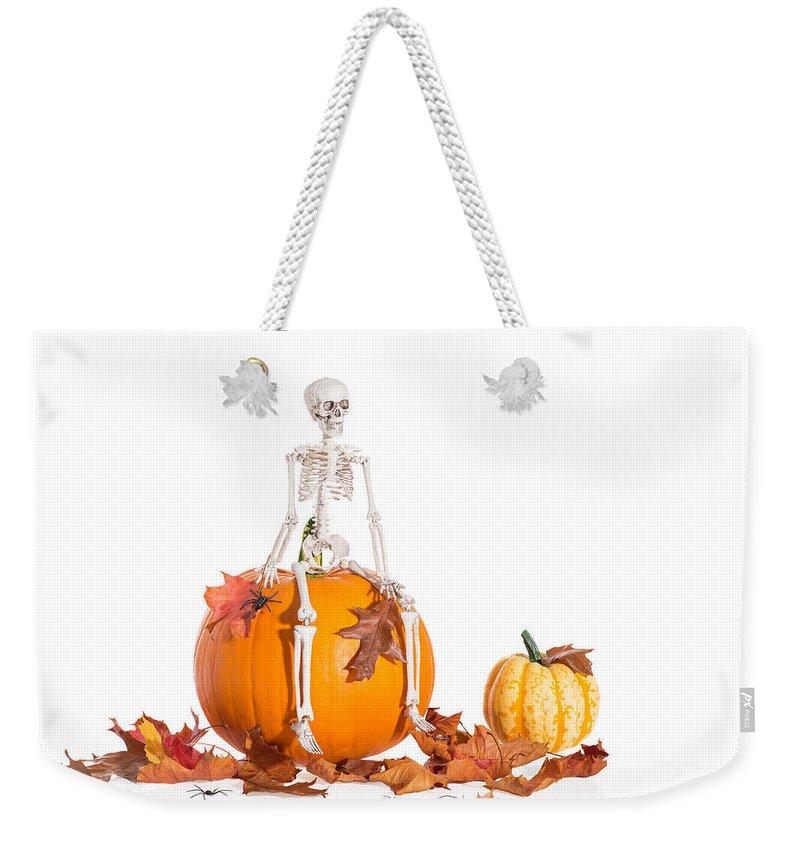 Skeleton Weekender Tote Bag featuring the photograph Skeleton Sitting On Pumpkin by Amanda Elwell
