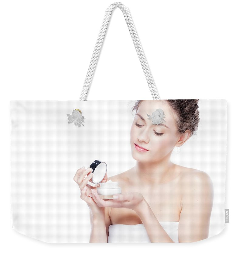 Skincare Weekender Tote Bag featuring the photograph Skin Care. Young Woman Opening A Creme Jar by Michal Bednarek