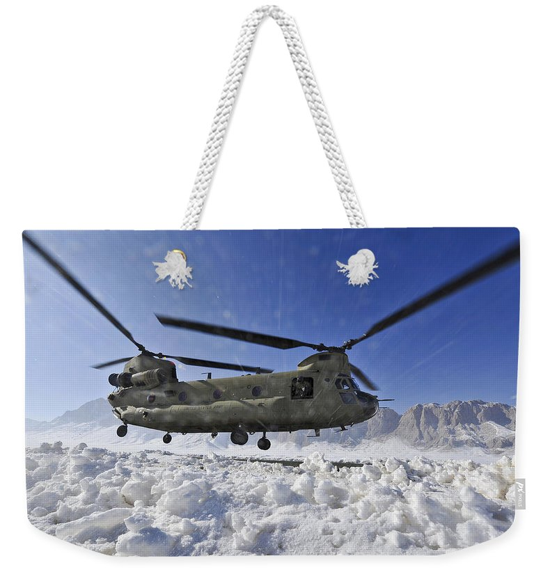 Ch-47 Weekender Tote Bag featuring the photograph Snow Flies Up As A U.s. Army Ch-47 by Stocktrek Images