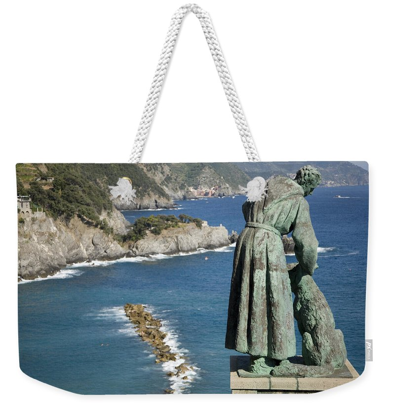Travel Weekender Tote Bag featuring the photograph Statue Of Saint Francis Of Assisi Petting A Dog by Ian Middleton