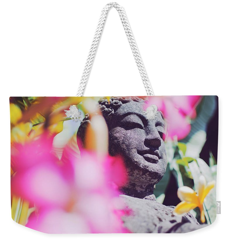 Artistic Weekender Tote Bag featuring the photograph Stone Carved Statue Of Buddha Surrounded With Colorful Flowers Bali, Indonesia by Srdjan Kirtic