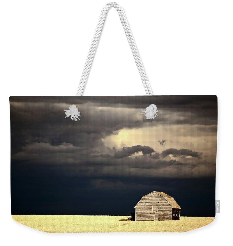 Abandoned Weekender Tote Bag featuring the digital art Storm Clouds Behind Abandoned Saskatchewan Barn by Mark Duffy