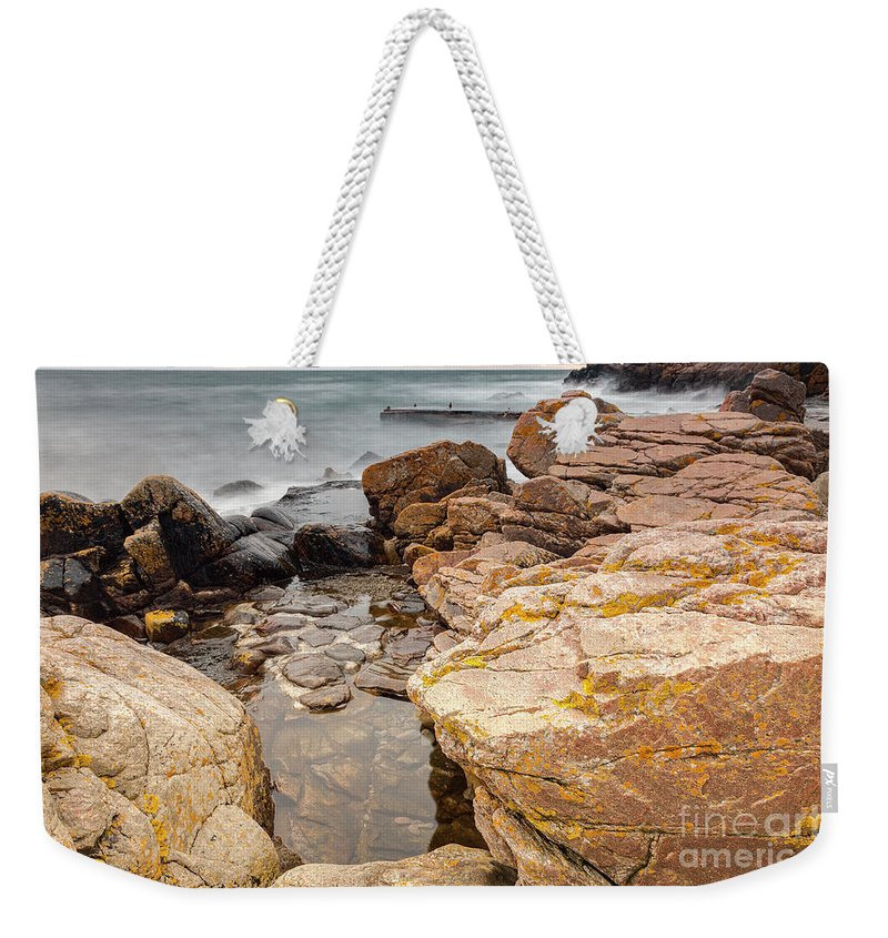 Sunset Weekender Tote Bag featuring the photograph Stormy Rock Beach by Sophie McAulay