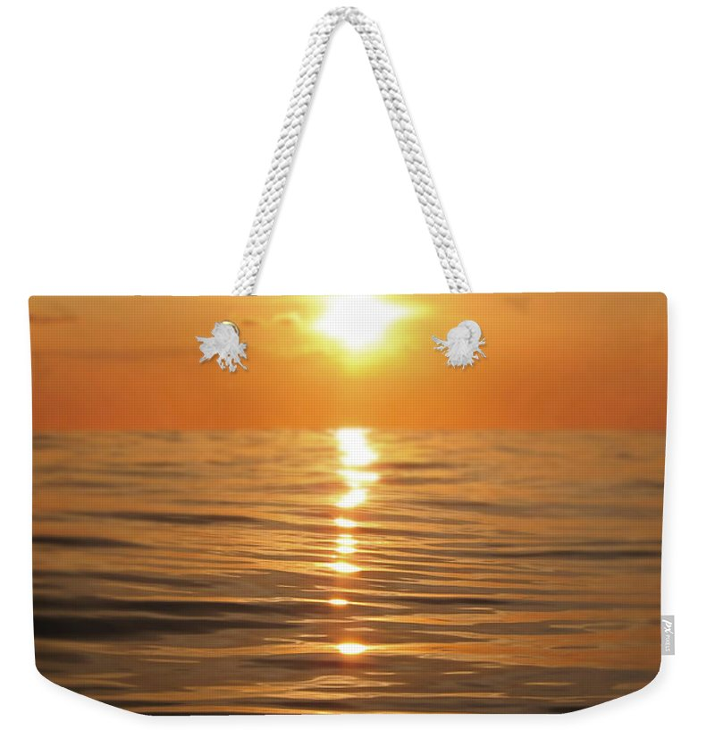 Golden Weekender Tote Bag featuring the photograph Sun setting over calm waters by Nicklas Gustafsson