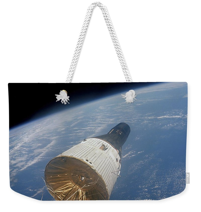 1965 Weekender Tote Bag featuring the photograph The Gemini-titan 7 Spacecraft In Earth by Stocktrek Images