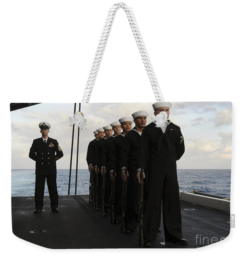 Military Weekender Tote Bag featuring the photograph The Honor Guard Stands At Parade Rest by Stocktrek Images