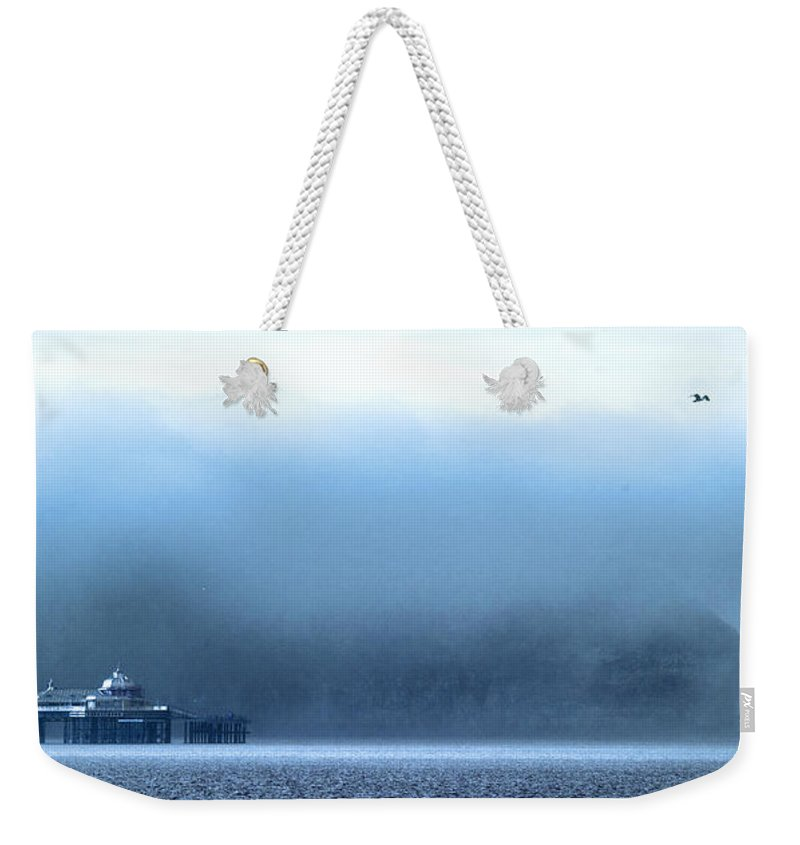 Pier Weekender Tote Bag featuring the photograph The Sea Mist Lifts To Reveal The Great Orme Behind Llandudno Pier by Mal Bray