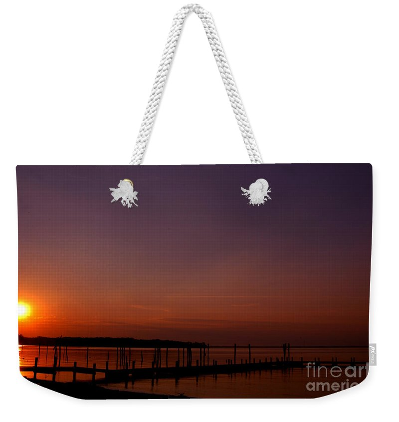 Clay Weekender Tote Bag featuring the photograph The Sun Sets Over The Water by Clayton Bruster