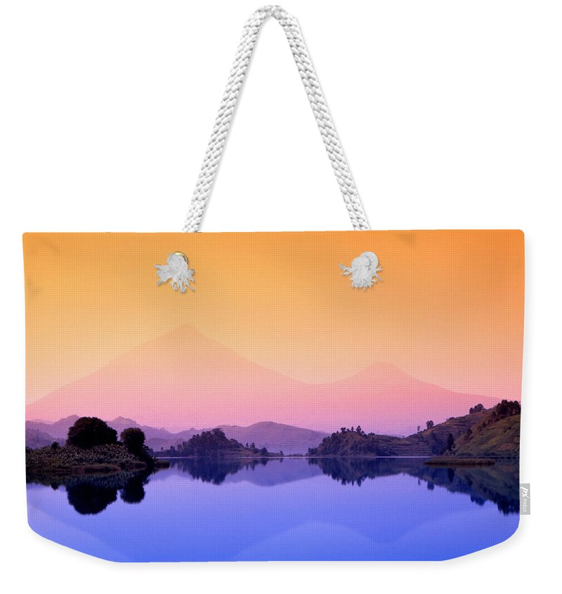 Lake Mutanda Weekender Tote Bag featuring the photograph The Virunga Mountains Rise Above Lake by David Pluth
