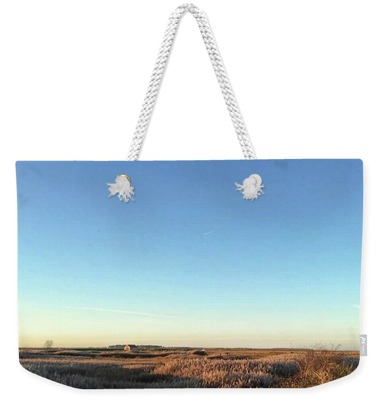 Natureonly Weekender Tote Bag featuring the photograph Thornham Marsh Lit By The Setting Sun by John Edwards
