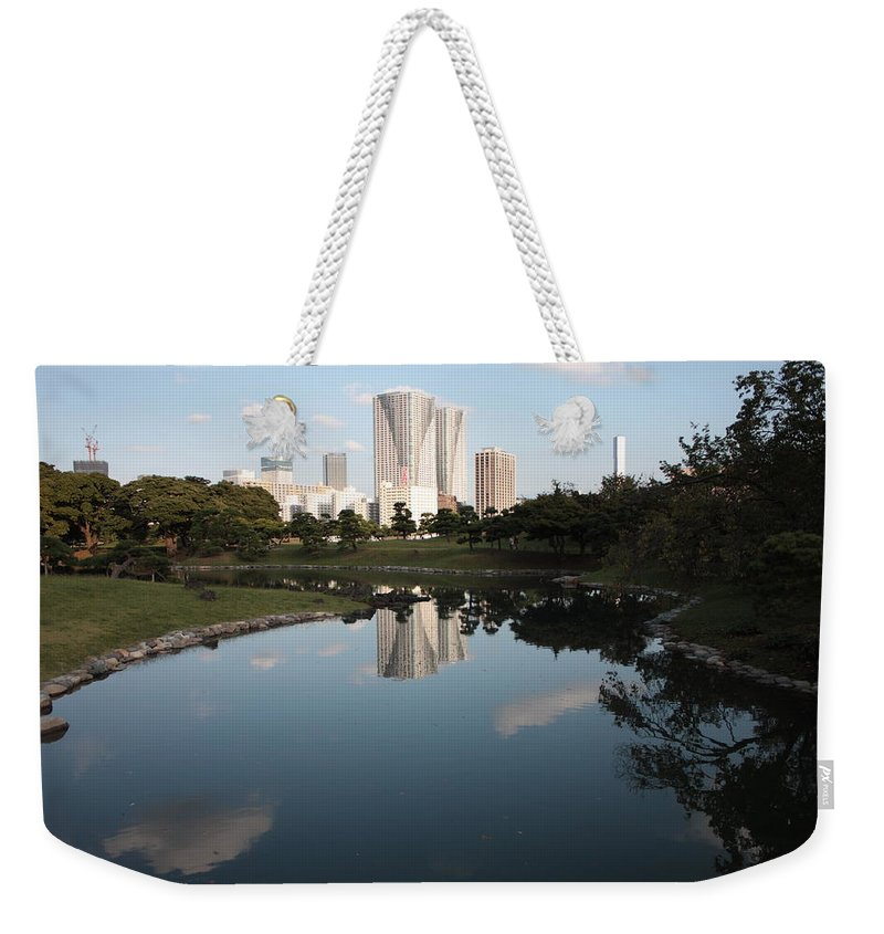 Tokyo Weekender Tote Bag featuring the photograph Tokyo Highrises With Garden Pond by Carol Groenen