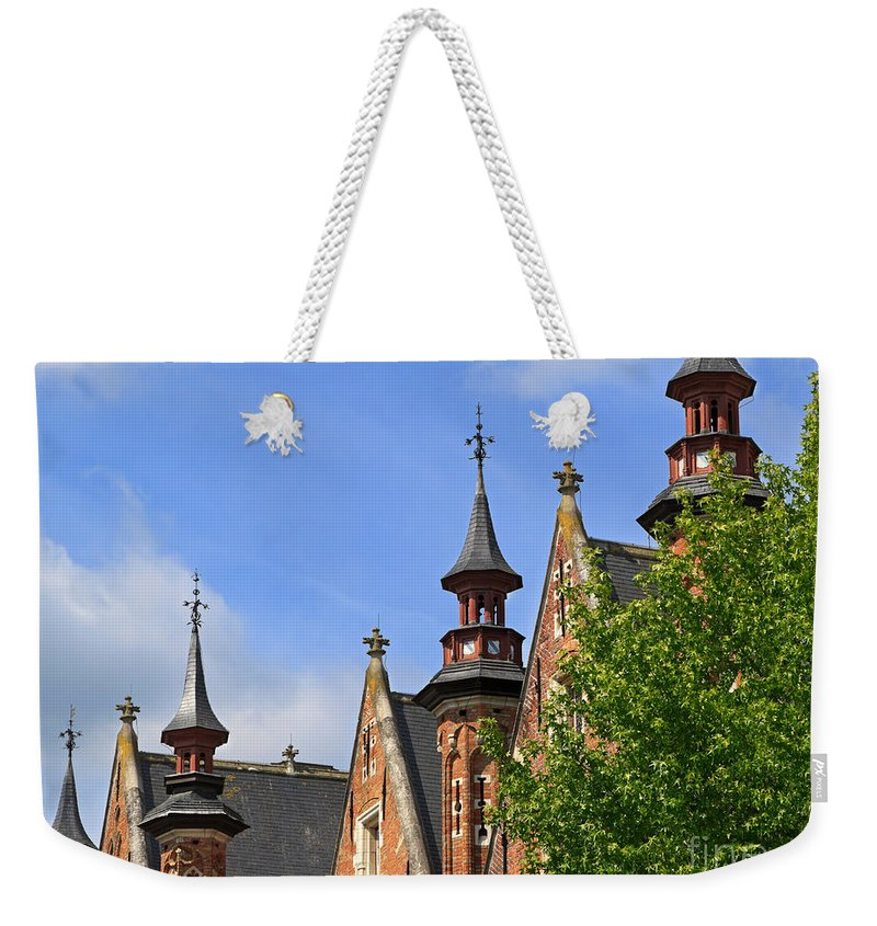 Steenhouwersdijk Weekender Tote Bag featuring the photograph Turrets And Roofs Beside Steenhouwersdijk Canal In Bruges by Louise Heusinkveld
