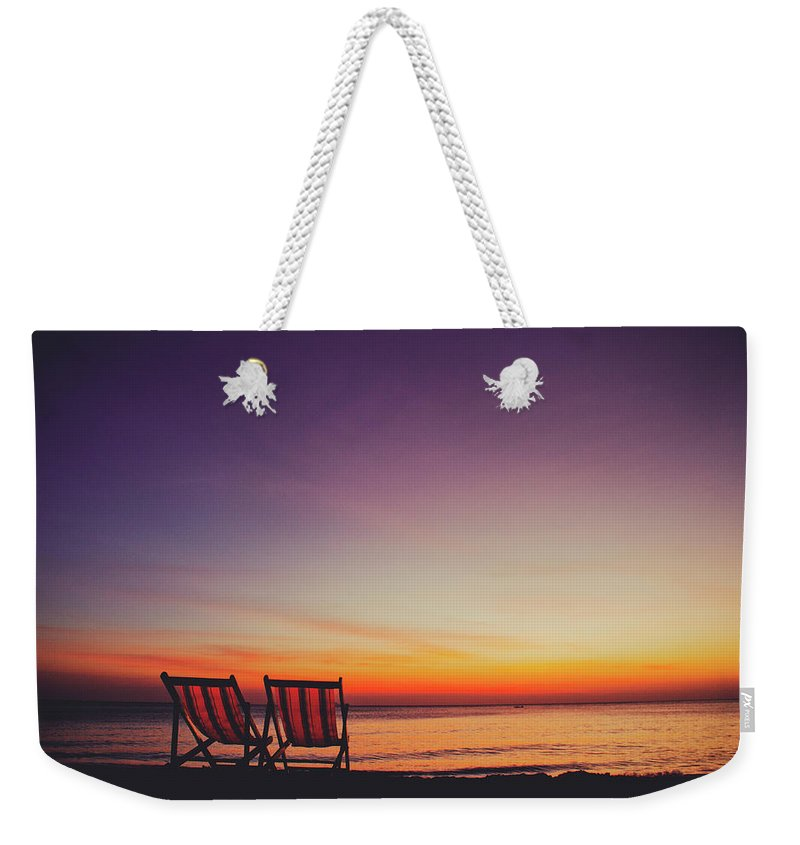 Appealing Weekender Tote Bag featuring the photograph Two Empty And Inviting Beach Chairs Next To The Sea During Beautiful Sunset On Koh Lanta Island by Srdjan Kirtic