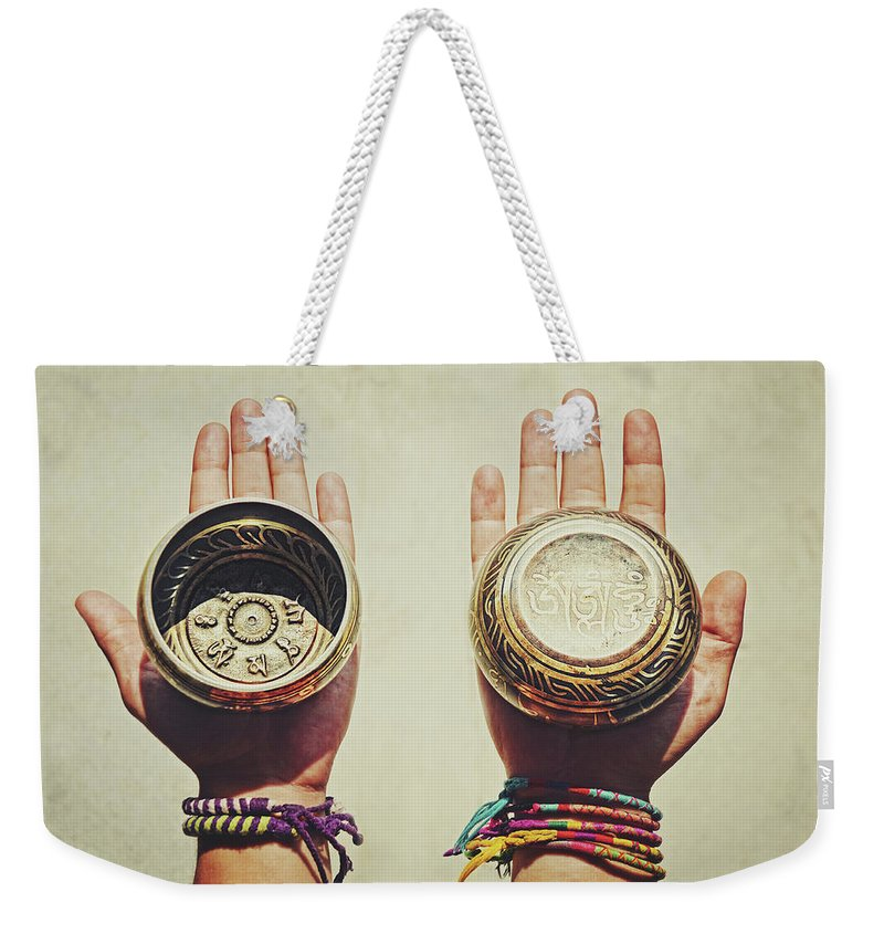 Aged Weekender Tote Bag featuring the photograph Two Hands Holding And Showing Both Sides Of Decorated Tibetan Singing Bowls by Srdjan Kirtic