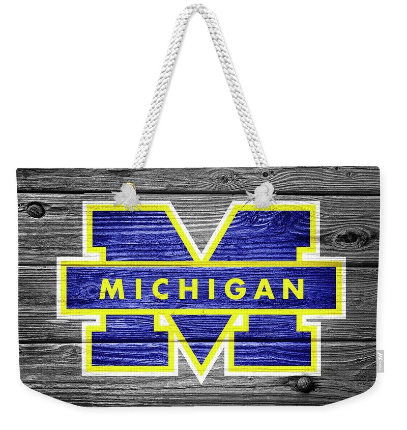 Football Weekender Tote Bag featuring the photograph University Of Michigan Wolverines Logo On Weathered Wood by John Stephens