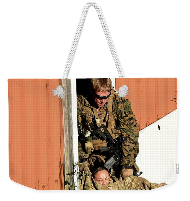 Exercise Emerald Warrior Weekender Tote Bag featuring the photograph U.s. Marine Drags An Injured Patient by Stocktrek Images