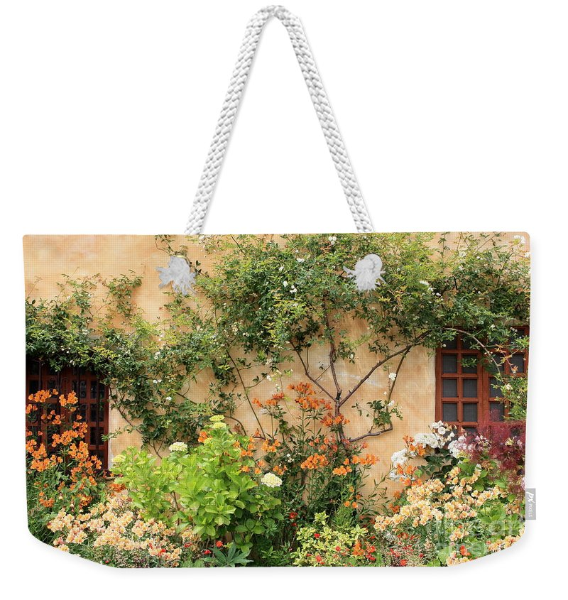 Carmel Mission Weekender Tote Bag featuring the photograph Warm Colors In Mission Garden by Carol Groenen