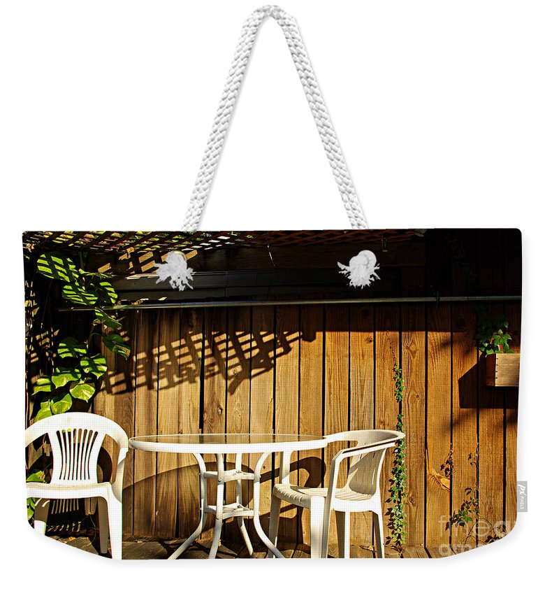 White Weekender Tote Bag featuring the photograph White Table With Chairs by Zal Latzkovich