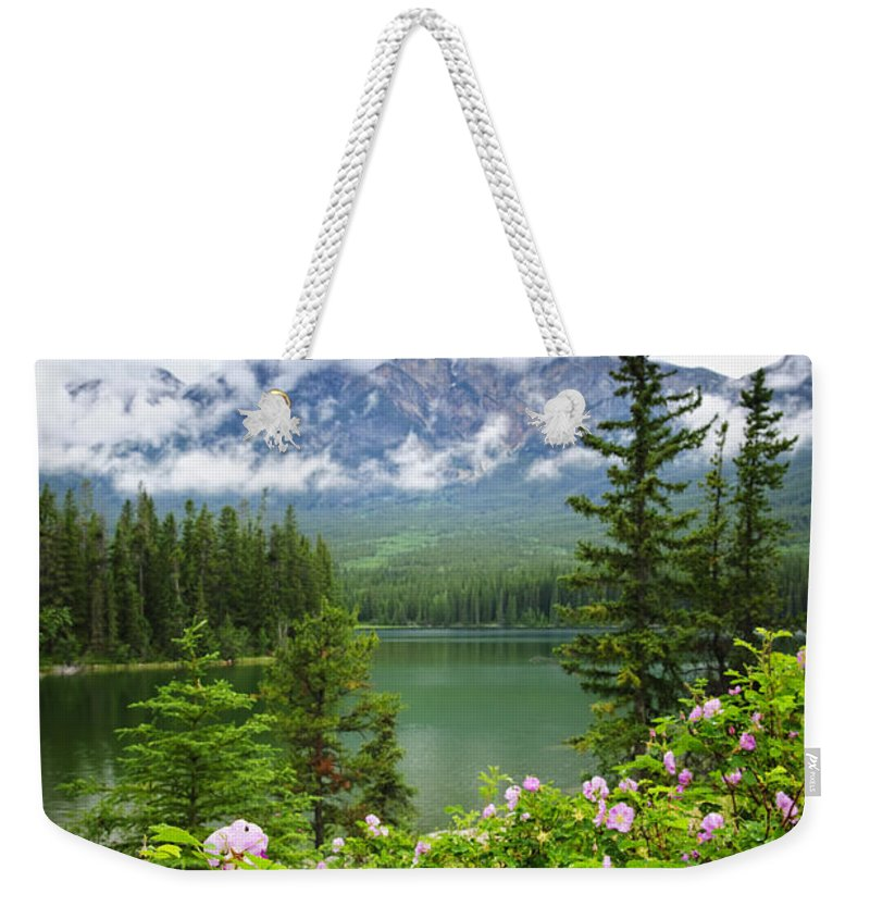 Wild Rose Weekender Tote Bag featuring the photograph Wild Roses And Mountain Lake In Jasper National Park by Elena Elisseeva