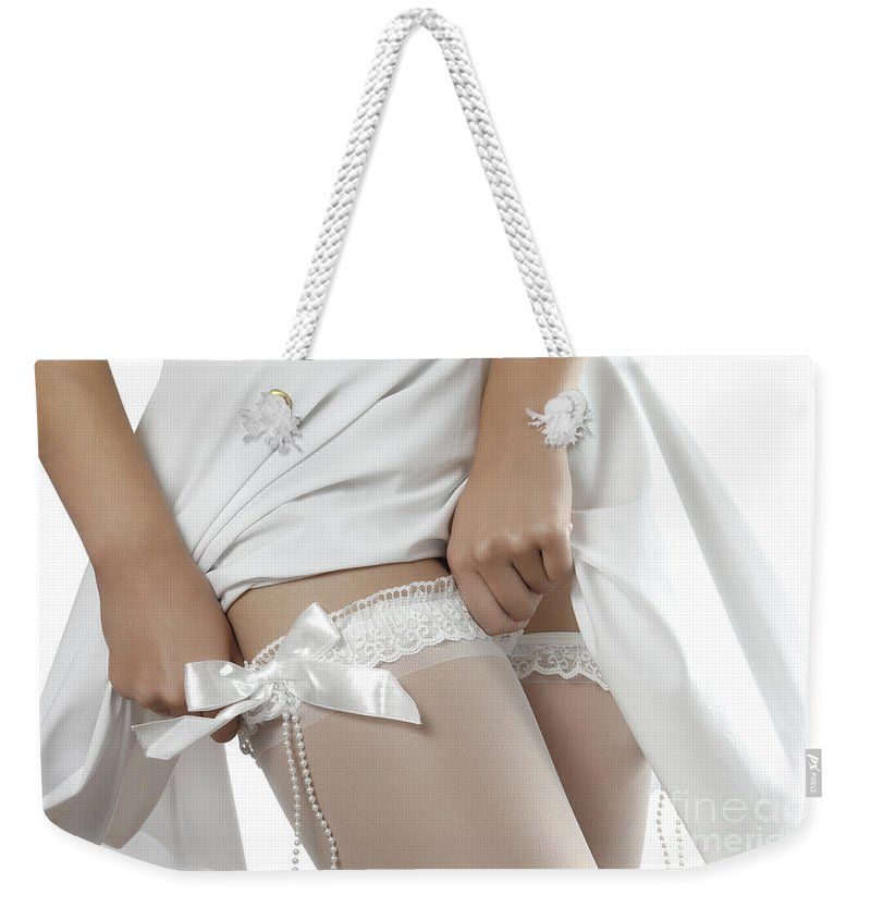 Stockings Weekender Tote Bag featuring the photograph Woman Putting On White Stockings by Maxim Images Prints