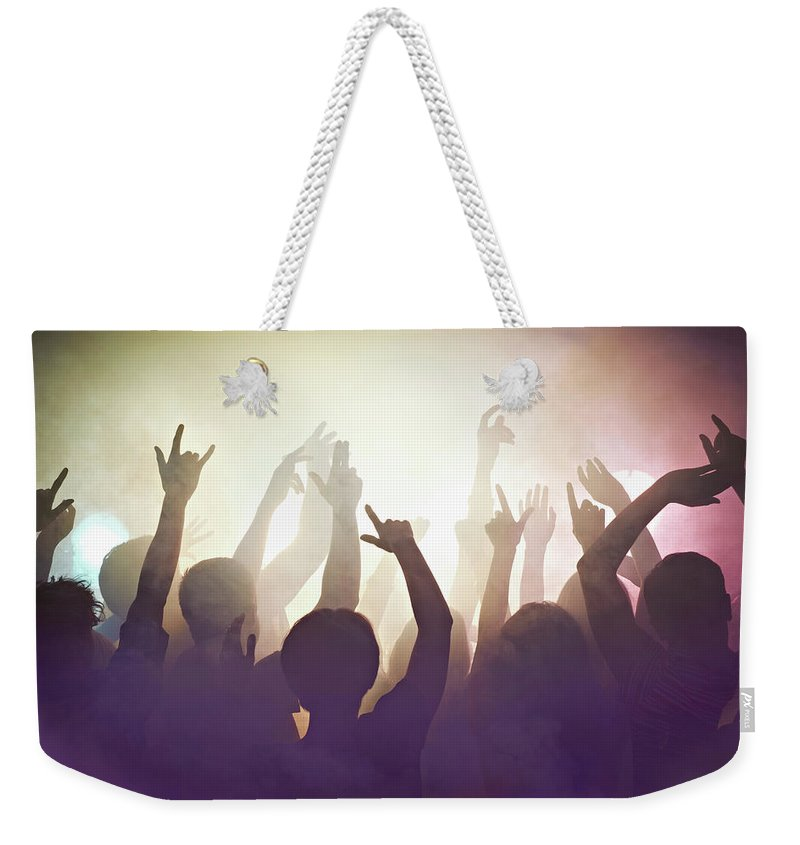 Young Men Weekender Tote Bag featuring the photograph Crowd Of People At Concert Waving Arms by Flashpop