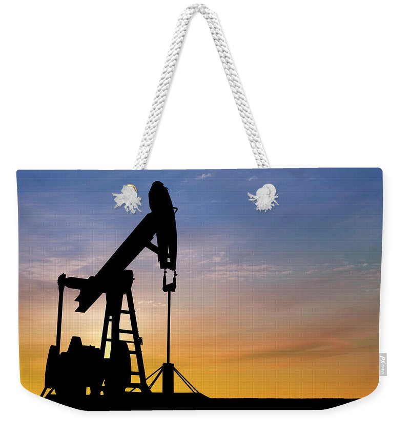 Dawn Weekender Tote Bag featuring the photograph Dawn Over Petroleum Pumps In The Desert by Grafissimo