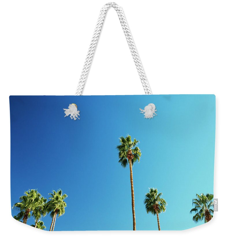 Clear Sky Weekender Tote Bag featuring the photograph Palm Trees Against Blue Sky by Micha Pawlitzki
