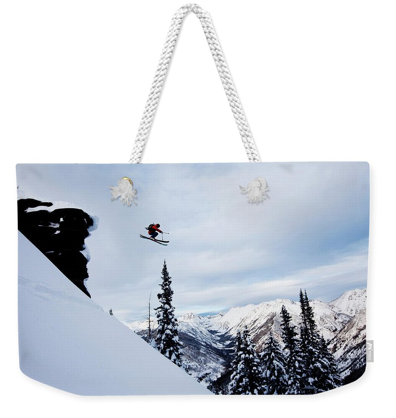 Skiing Weekender Tote Bag featuring the photograph A Athletic Skier Jumping Off A Cliff In by Patrick Orton