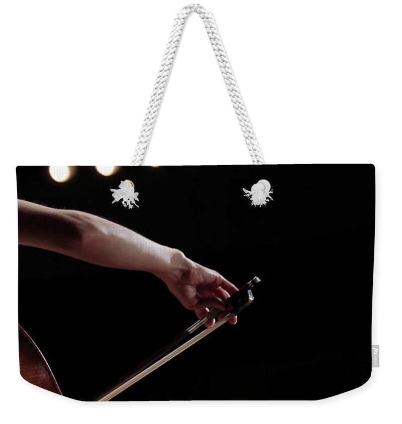 Mature Adult Weekender Tote Bag featuring the photograph A Female Cellist Hand Playing by Sot
