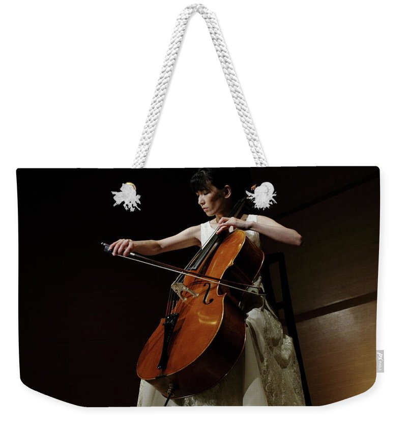 Mature Adult Weekender Tote Bag featuring the photograph A Female Cellist Playing Cello On Stage by Sot