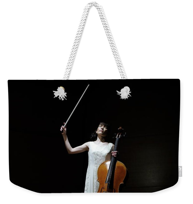 Human Arm Weekender Tote Bag featuring the photograph A Female Cellist Raising Bow Of Cello by Sot