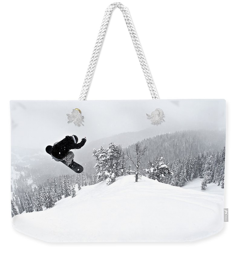 Recreational Pursuit Weekender Tote Bag featuring the photograph A Man On A Snowboard Flies Through The by Derek Diluzio