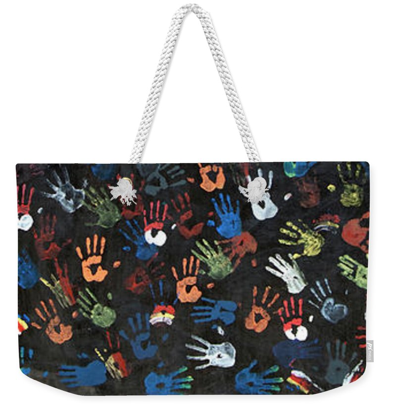 Child Weekender Tote Bag featuring the photograph A Painting Of Colorful Handprints by Khananastasia
