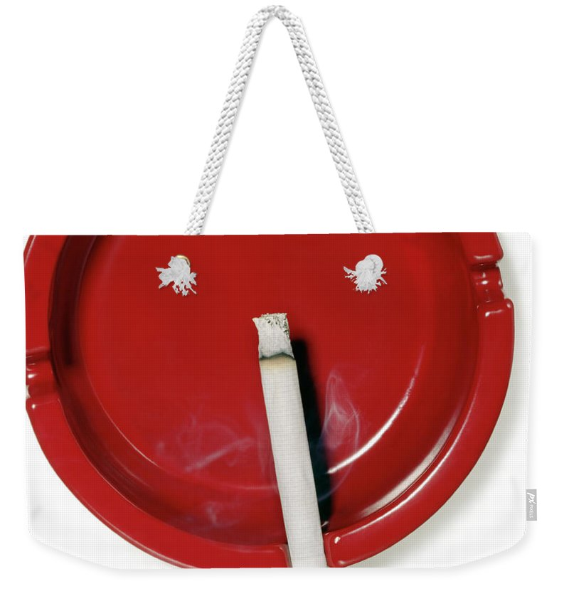 White Background Weekender Tote Bag featuring the photograph A Red Ashtray With A Burning Cigarette by Steve Wisbauer