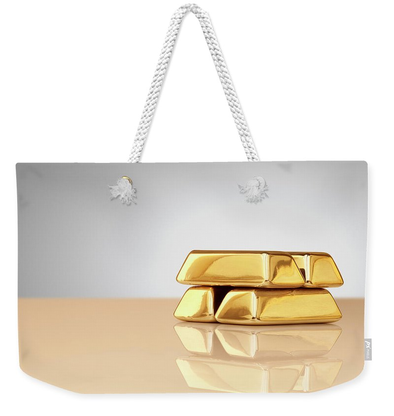 Four Objects Weekender Tote Bag featuring the photograph A Stack Of Four Gold Ingots by Anthony Bradshaw