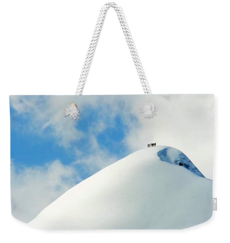 The End Weekender Tote Bag featuring the photograph A Team Of People Climbing A Snowy by Lopurice