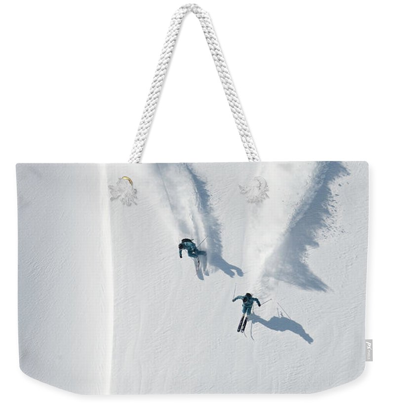 Crash Helmet Weekender Tote Bag featuring the photograph Aerial View Of Two Skiers Skiing by Creativaimage