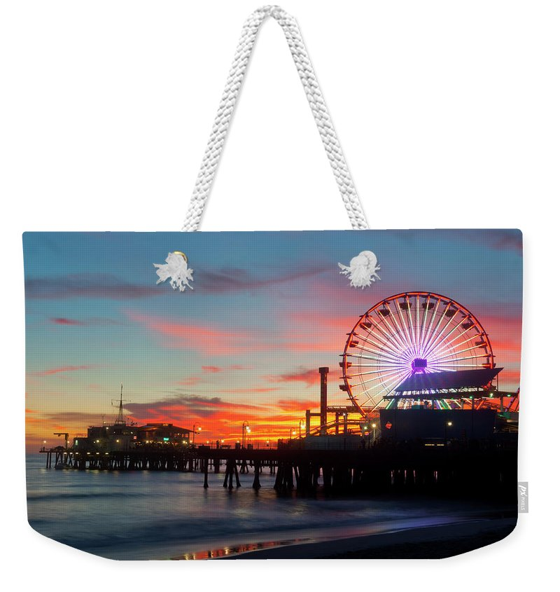 Scenics Weekender Tote Bag featuring the photograph Amusement Park On Waterfront At Night by Blend Images/pete Saloutos