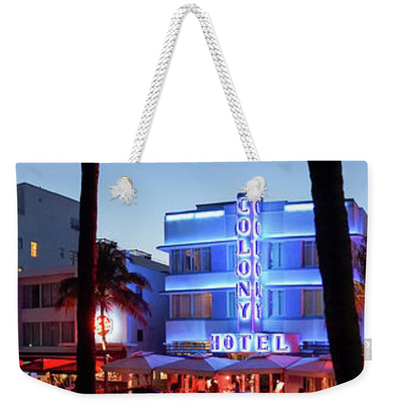 Panoramic Weekender Tote Bag featuring the photograph Art Deco Hotels On Ocean Drive At Dusk by Buena Vista Images