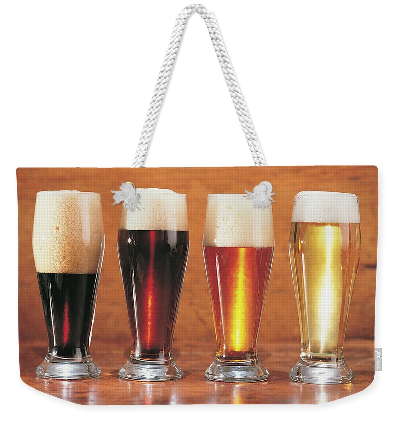 Stout Weekender Tote Bag featuring the photograph Assorted Beers And Ales by Comstock
