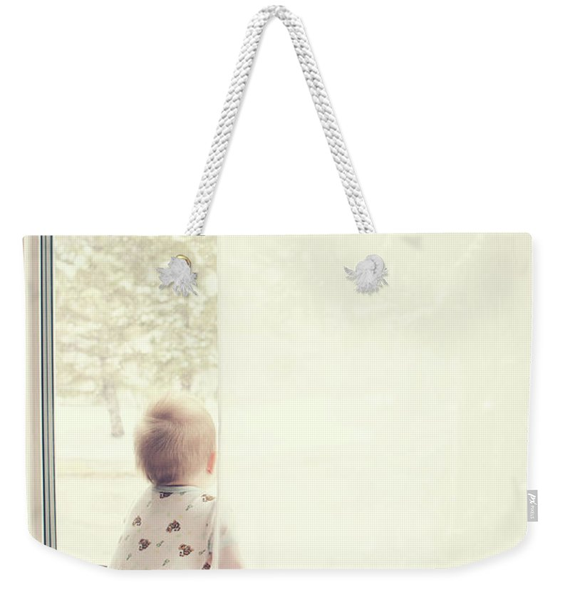 People Weekender Tote Bag featuring the photograph Baby At Window Watching Snow Fall by Www.reneebonuccelli.com