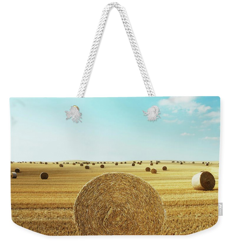 Field Stubble Weekender Tote Bag featuring the photograph Bales Of Hay In Harvested Field by Henrik Sorensen