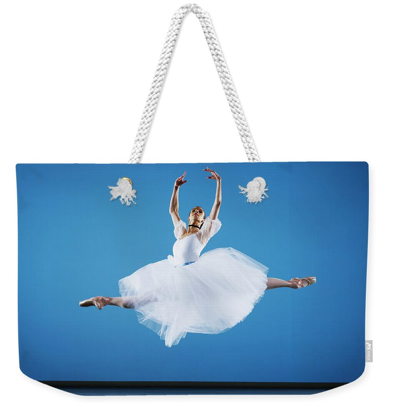 Ballet Dancer Weekender Tote Bag featuring the photograph Ballerina Leaping On Stage, Arms Raised by Thomas Barwick