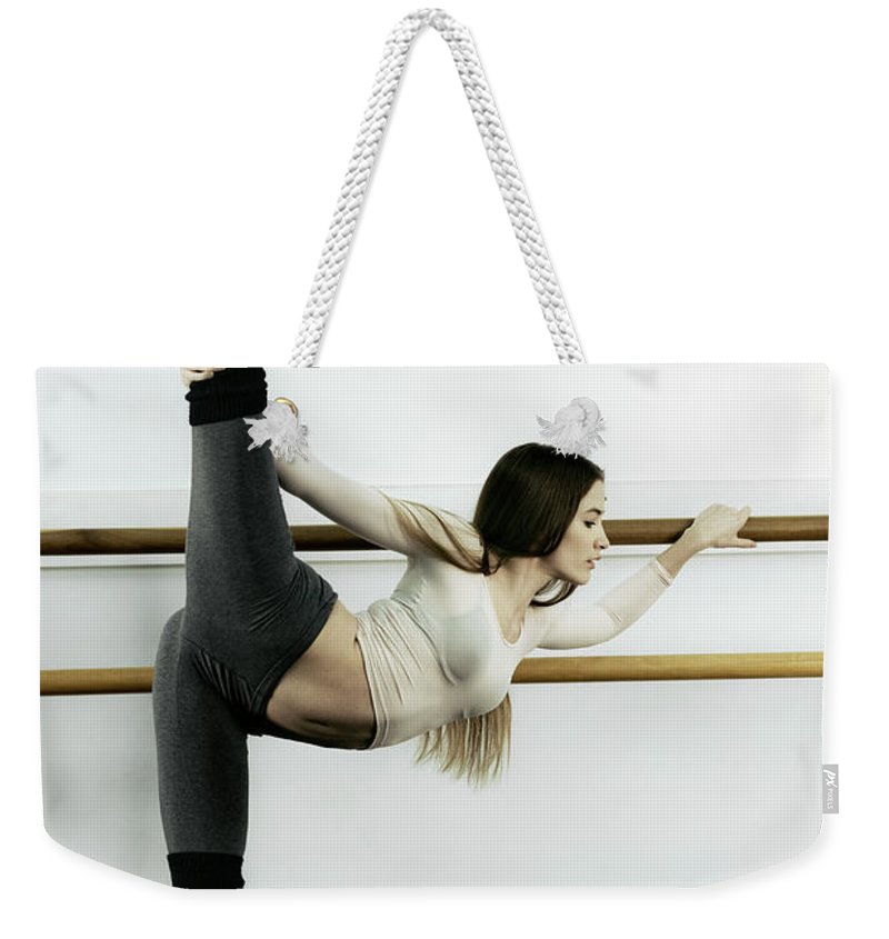 Ballet Dancer Weekender Tote Bag featuring the photograph Ballet Dancer Stretching In Dance by Patrik Giardino