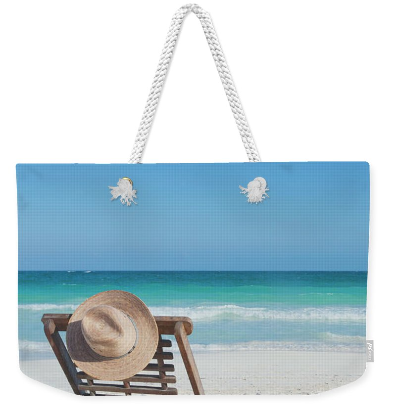 Scenics Weekender Tote Bag featuring the photograph Beach Chair With A Hat On An Empty Beach by Sasha Weleber