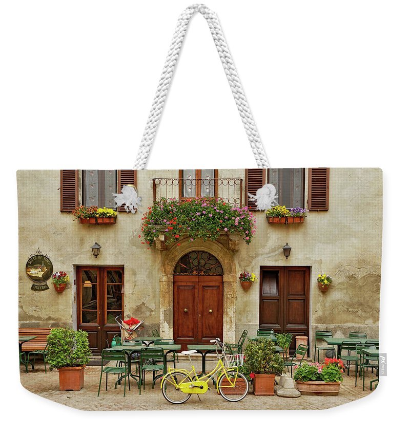 Pienza Weekender Tote Bag featuring the photograph Bicycle In Front Of Small Cafe, Tuscany by Adam Jones