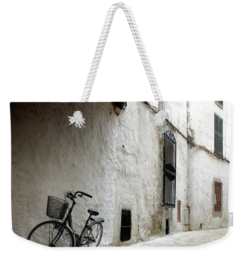 Tranquility Weekender Tote Bag featuring the photograph Bicycle Leaning Wall by Antonio R. Ramos