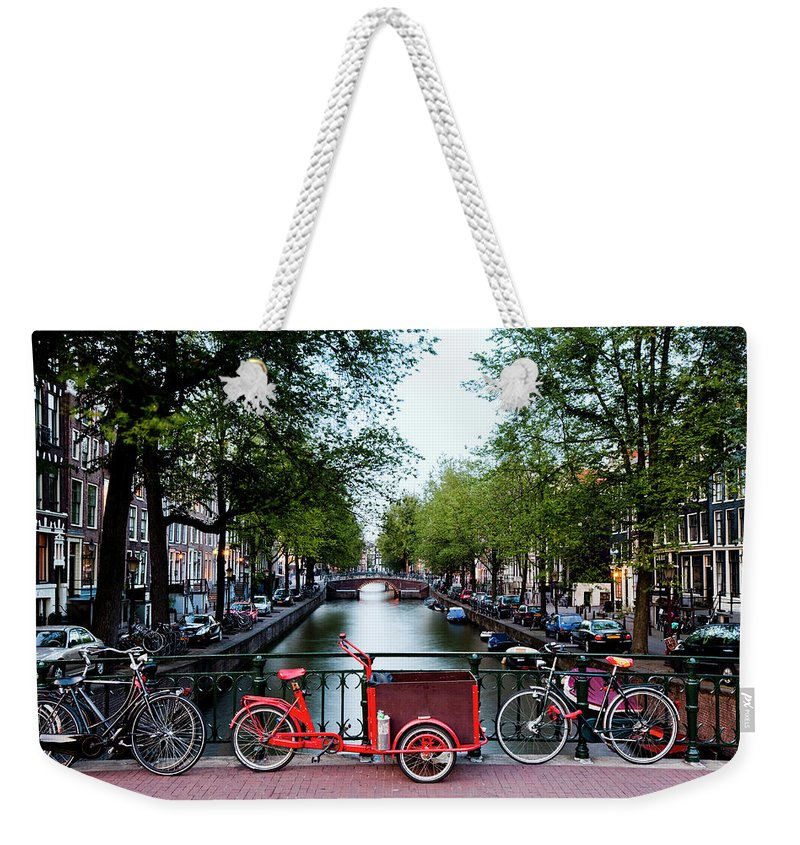 North Holland Weekender Tote Bag featuring the photograph Bicycles Parked On Bridge Over by Jorg Greuel