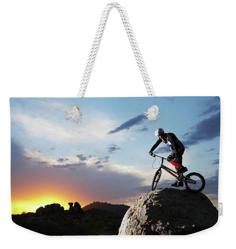 Sports Helmet Weekender Tote Bag featuring the photograph Bike Rider Balancing On Rock Boulder by Thomas Northcut