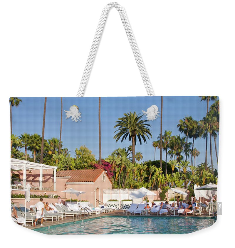 Tranquility Weekender Tote Bag featuring the photograph Blue-bottomed Pool Beneath Palm Trees by Barry Winiker